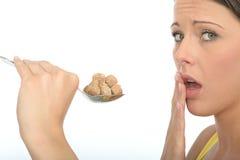 拿着几勺红糖立方体的不快乐的谨慎少妇 免版税库存照片