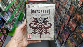 拿着几天在索尼Playstation 4控制台的人去的专辑计算机游戏在商店 图库摄影