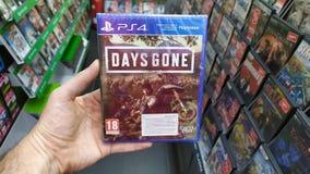 拿着几天在索尼Playstation 4控制台的人去的计算机游戏在商店 免版税库存照片