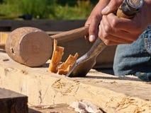 拿着凿子和短槌有芯片的手从木材榫眼出来 免版税库存照片