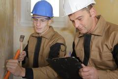 拿着凿子和锤子的年轻建造者 库存图片