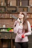 拿着刀子和一个红色蕃茄的妇女 在家烹调在厨房里的少妇 健康的食物 饮食 库存图片