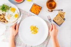 拿着刀子和叉子和白色板材有维生素药片的顶视图女性手在服务的木桌上与早餐膳食 Pi 免版税库存图片
