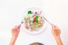 拿着刀子和叉子在板材的顶视图女性手用虚幻的沙拉从回收废,综合性成份 概念o 免版税图库摄影