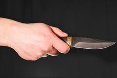 拿着刀子的人的手 库存照片