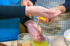 拿着分开的鸡蛋的妇女手 烹调的概念 免版税库存图片
