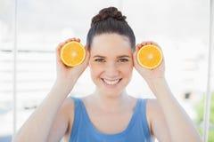 拿着切片桔子的运动服的快乐的苗条妇女 免版税库存图片