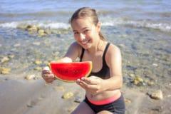 拿着切片西瓜的海滩的年轻美女 黑泳装的青少年在海滩微笑着 免版税库存图片