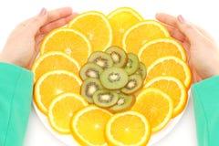 拿着切的果子的手 库存图片