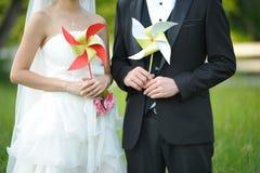 拿着别针轮子的新娘和新郎 免版税库存图片