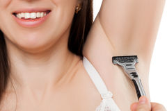 拿着剃须刀的秀丽微笑的少妇刮腋窝sk 免版税图库摄影