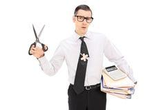 拿着剪刀和堆文件的会计 免版税库存照片