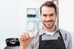 拿着剪刀的英俊的美发师 库存照片
