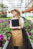 拿着剪贴板的可爱的女性花匠由花 图库摄影