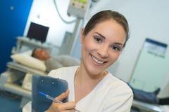 拿着剪贴板的美丽的微笑的女性医生 库存图片