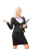 拿着剪贴板和打手势与的年轻白肤金发的女实业家 免版税库存图片