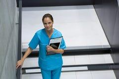 拿着剪贴板和数字式片剂在楼梯的女性外科医生画象 库存照片