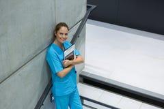 拿着剪贴板和数字式片剂在楼梯的女性外科医生画象 免版税库存图片