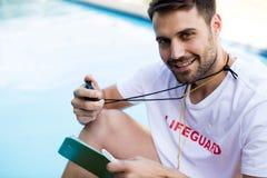 拿着剪贴板和秒表的救生员画象在游泳池边 免版税库存图片