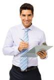 拿着剪贴板和笔的愉快的商人 免版税库存照片