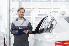 拿着剪贴板的微笑的男性汽车修理工画象,当支持在维修车间时的汽车 免版税库存图片