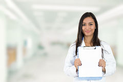 拿着剪贴板的愉快的微笑的医生站立在医院走廊 免版税图库摄影