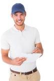拿着剪贴板的愉快的送货人 免版税库存图片