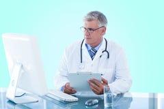 拿着剪贴板的男性医生的综合3d图象,当看计算机显示器时 免版税库存图片