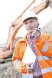 拿着剪贴板的监督员,当使用携带无线电话在建造场所时 免版税库存图片