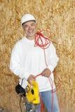 拿着力量锯和一根红色电导线的一名愉快的男性建筑工人的画象 免版税库存照片