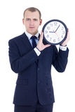 拿着办公室时钟的西装的年轻人被隔绝在丝毫 免版税图库摄影