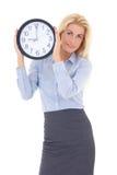 拿着办公室时钟的西装的年轻美丽的妇女 图库摄影