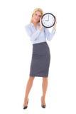 拿着办公室时钟isol的西装的年轻美丽的妇女 库存图片
