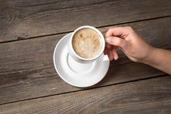 拿着加奶咖啡杯子的妇女 温暖的杯子在妇女手上 库存图片