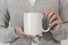 拿着加奶咖啡杯子的手 创造性的设计品牌的大模型 免版税库存图片