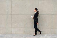 拿着加奶咖啡杯子的美丽的衣服妇女 免版税库存照片