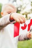 拿着加拿大旗子的小的白肤金发的白种人男孩儿童手特写镜头画象  图库摄影
