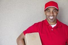 拿着包裹的一个非裔美国人的送货人的画象对墙壁 免版税库存图片