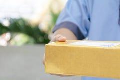拿着包裹的送货人的特写镜头手交付 免版税库存照片