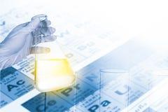 拿着化工测试的科学家烧瓶在化学实验室 免版税库存照片