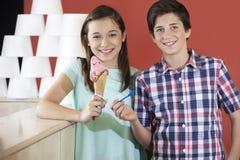 拿着匙子和草莓冰淇凌的兄弟和姐妹 免版税库存照片