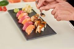 拿着匙子用寿司的芝麻的厨师 库存照片