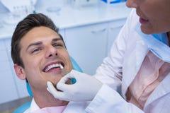 拿着医疗设备的牙医,当审查患者在诊所时 库存照片