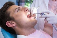 拿着医疗设备的牙医,当给治疗患者在诊所时 库存图片