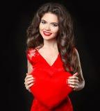 拿着华伦泰的心脏的红色礼服的美丽的愉快的微笑的女孩 有长的卷曲在b隔绝的发型和红色嘴唇的浅黑肤色的男人 免版税库存图片