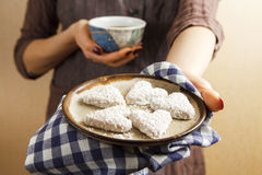 拿着华伦泰饼干和咖啡的手 免版税库存照片
