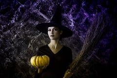拿着南瓜和笤帚的万圣夜巫婆 免版税库存照片