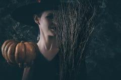 拿着南瓜和笤帚的万圣夜巫婆 免版税图库摄影