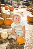 拿着南瓜的可爱的女婴在南瓜补丁 免版税库存图片