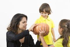 拿着南瓜的愉快的家庭 免版税图库摄影